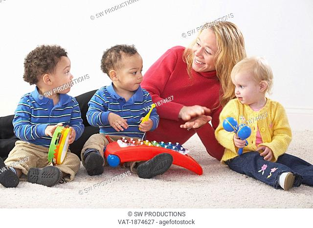 Knoxville, Tennessee, United States Of America, A Woman Playing With Three Young Children Who Have Instruments
