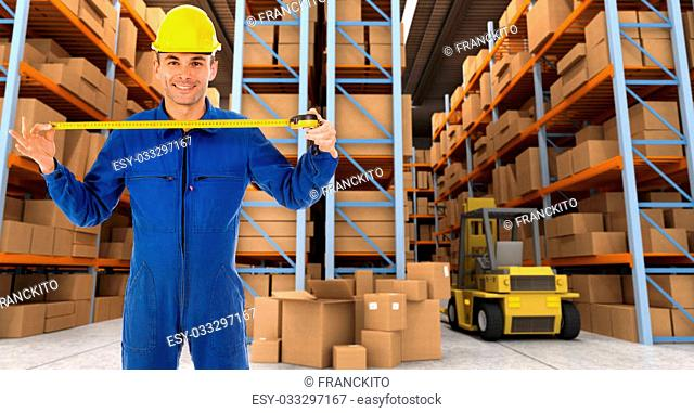 Man with helmet and blue overalls in a distribution warehouse extending a tape measure