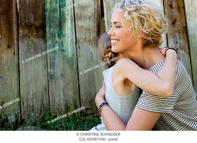 Mother and daughter hugging, wooden fence in background