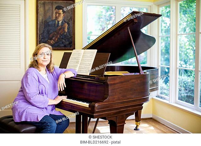 Caucasian musician leaning on piano