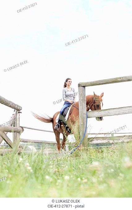 Woman horseback riding in fenced rural pasture