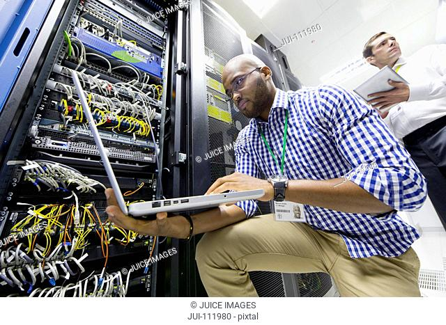 Technicians with laptop and digital tablet checking server in data centre