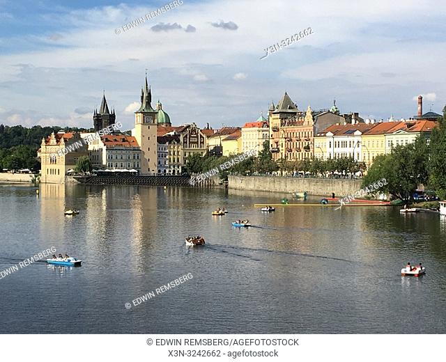 People ride paddle boats on the Vltava river with the city of Prague behind them, Czech Republic