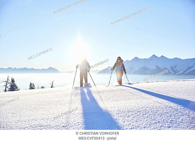 Austria, Tyrol, snowshoe hikers at sunrise