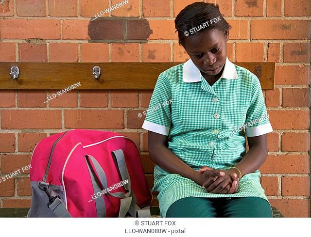 Schoolgirl sits alone outside her classroom, KwaZulu Natal Province, South Africa