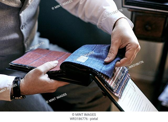 A tailor looking at fabric samples in a book, tweed and wool for men's clothes