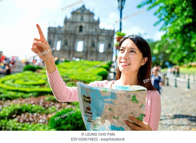 Woman holding city map and finger pointing the location