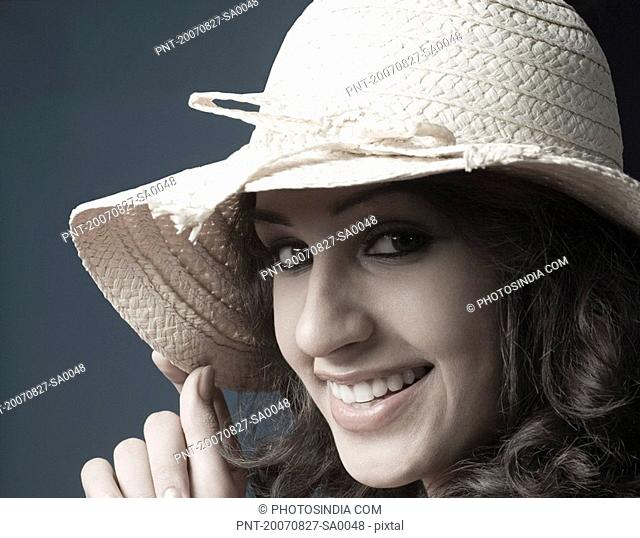 Portrait of a young woman wearing a straw hat and smiling
