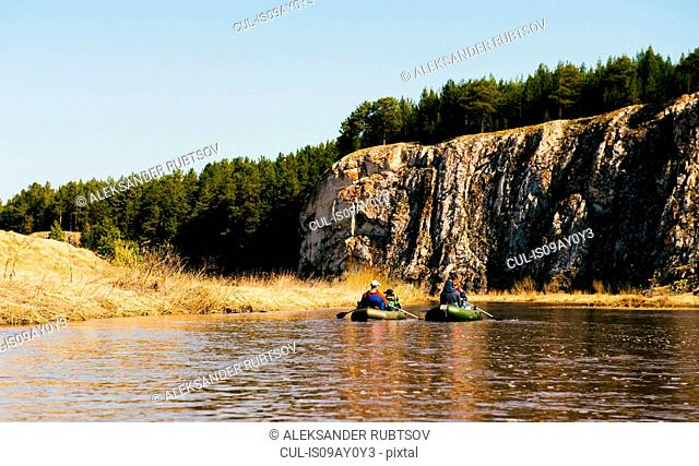 Group of friends on river in dinghies by rock face