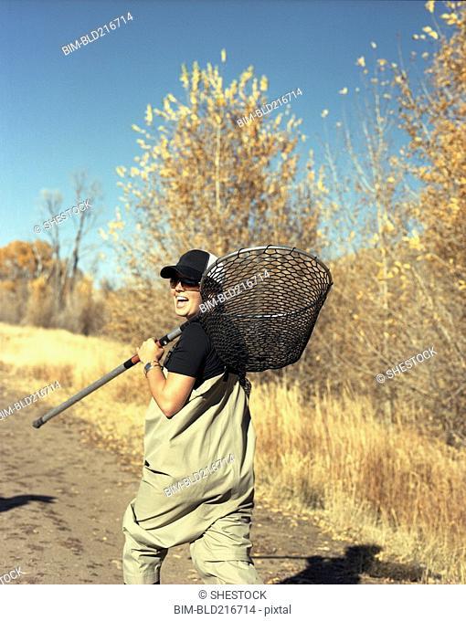 Happy woman carrying fishing net on dirt path