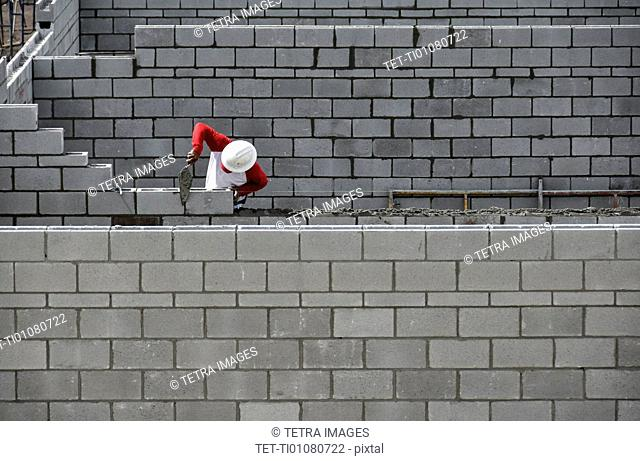 Bricklayer working on brick wall