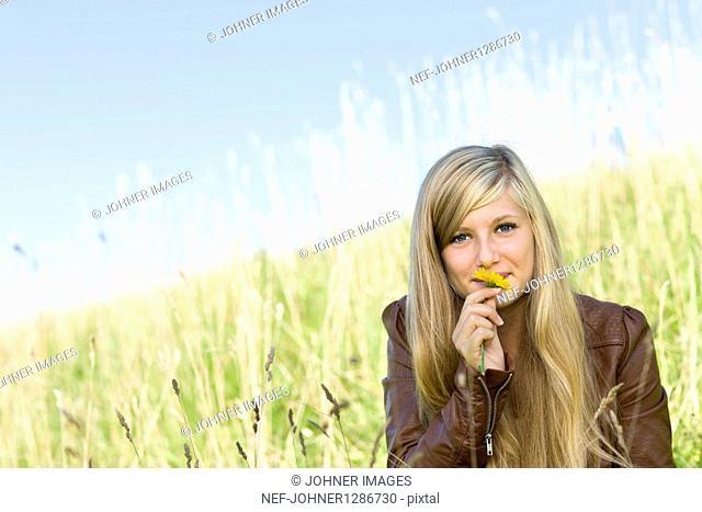 Portrait of girl smelling marigold in field