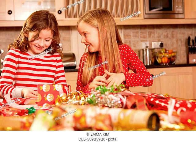 Two girls wrapping christmas presents at table