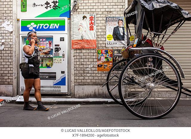 rickshaw talking on phone, in 2 chome street,next to Sensoji Temple, Asakusa, Tokyo, Japan, Asia