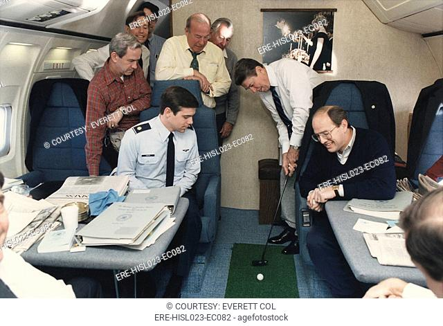 President Reagan putting a golf ball around Air Force One while flying to Geneva Summit with Soviet Union's Gorbachev. Standing to Reagan's right are George...