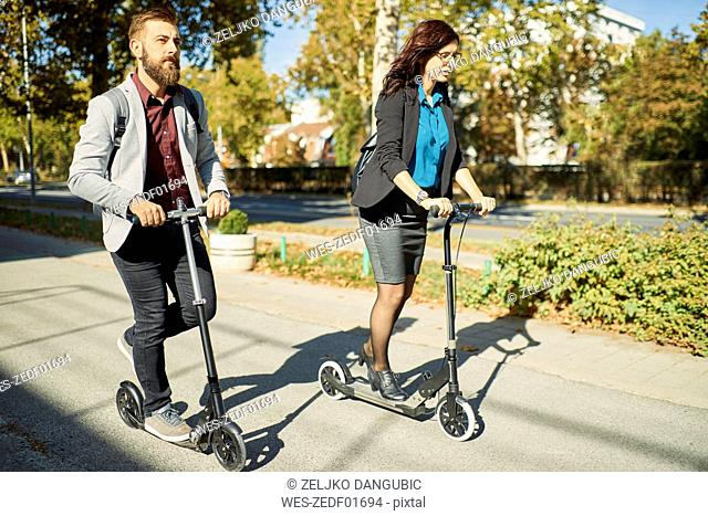 Businessman and businesswoman riding scooter