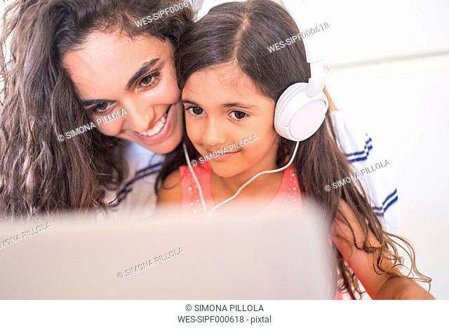 Happy teenage girl and her little sister with laptop and headphones
