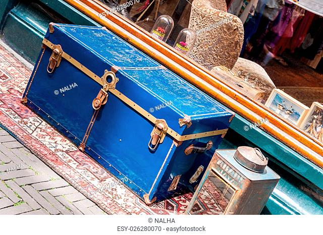 Large, old, blue travel chest at the window of a shop for antiques and trinkets