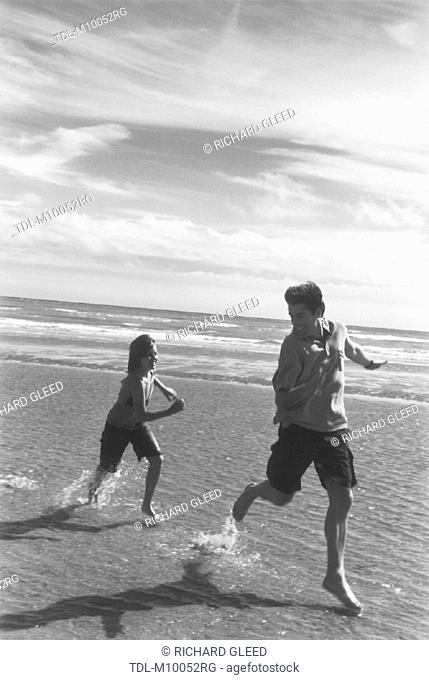 A father being chased along the beach by his daughter
