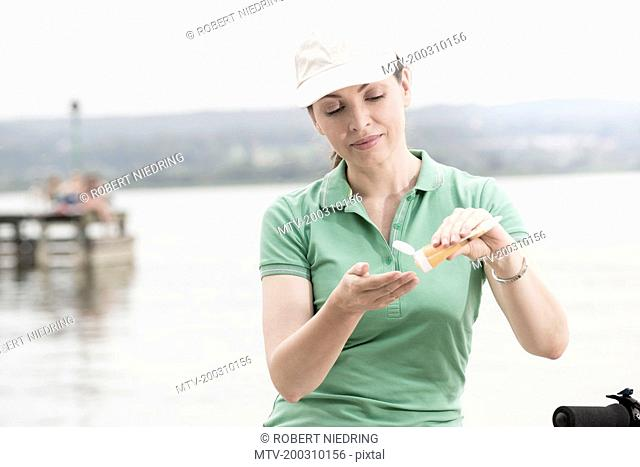 Mature woman applying sun cream by lake, Bavaria, Germany
