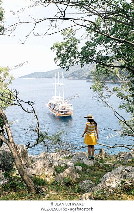 Croatia, Cres, woman standing at the coast looking at the sea with sailing ship