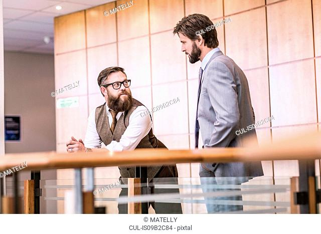 Two businessmen talking on office balcony