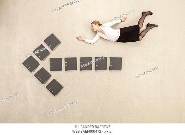 Businesswoman flying above files forming arrow sign