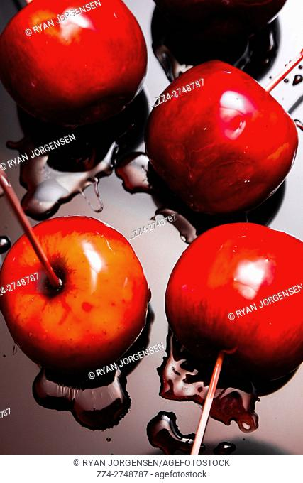 Directly above shot of light beaming on fresh red lollipop toffee apples with syrup spilled on surface