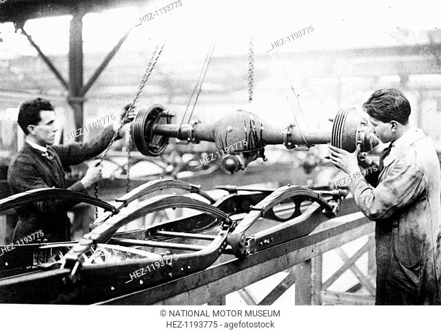 Two men at work on the production line, Cubitt factory, c1920-c1921. They appear to be lowering an axle into position onto a car chassis