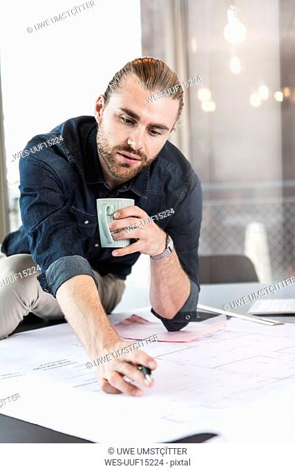 Young businessman working on plan at desk in office
