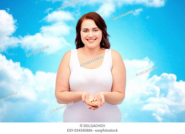 weight loss, diet, slimming, medicine and people concept - happy plus size woman in underwear with pills over blue sky and clouds background