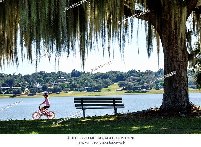 Florida, Lake Wales, Lake Wailes, public park, Spanish moss, hanging, girl, riding, bicycle, safety helmet, bench, water, scenery