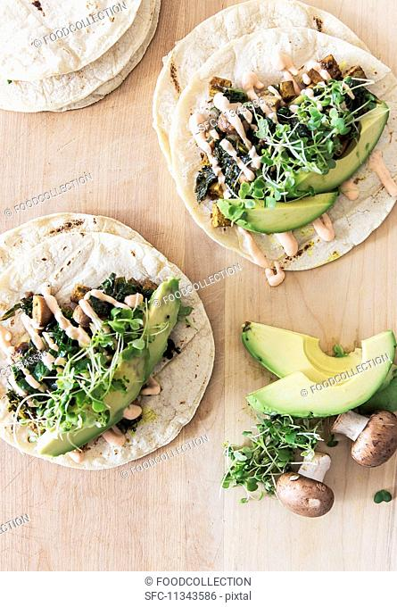 Vegetarian tacos with vegan mayonnaise on a kitchen table with avocado, mushrooms and beans sprouts