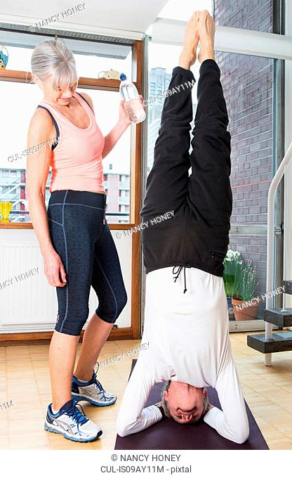 Woman beside husband doing headstand at home