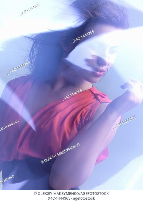 Futuristic dynamic beauty photo of a young woman wearing a red dress in shiny neon light settings  The photo was not digitally manipulated