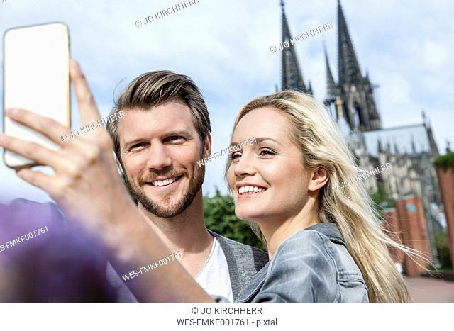 Germany, Cologne, young couple taking a selfie with smartphone