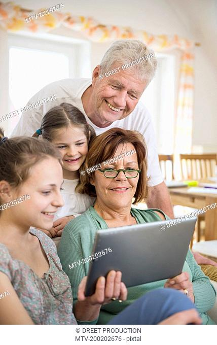 Grandparents and granddaughters looking in digital tablet, smiling