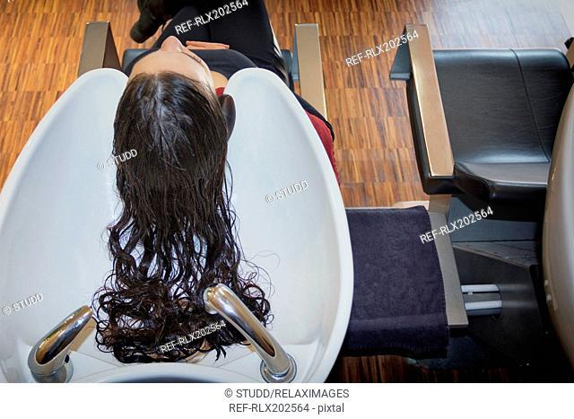 Hairdresser woman washing hair salon customer sink