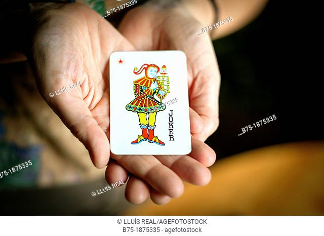 hands showing Joker, the deck of cards
