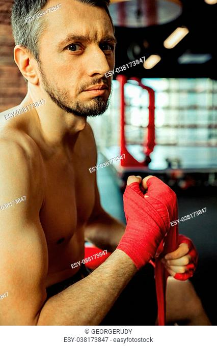 Blue eyed middle aged boxer wrapping his hands, ready to fight; looking at camera