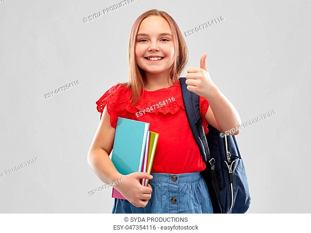 student girl with books and bag showing thumbs up