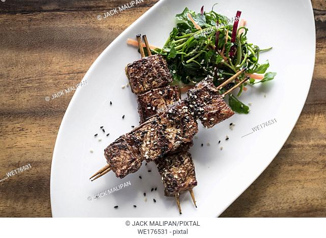 asian spicy sweet soy sauce and sesame seed grilled barbecue pork skewers in singapore restaurant