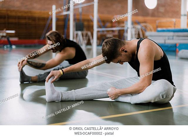 Two young men stretching in gym