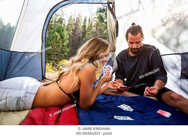 Young couple playing cards in tent, Lake Tahoe, Nevada, USA