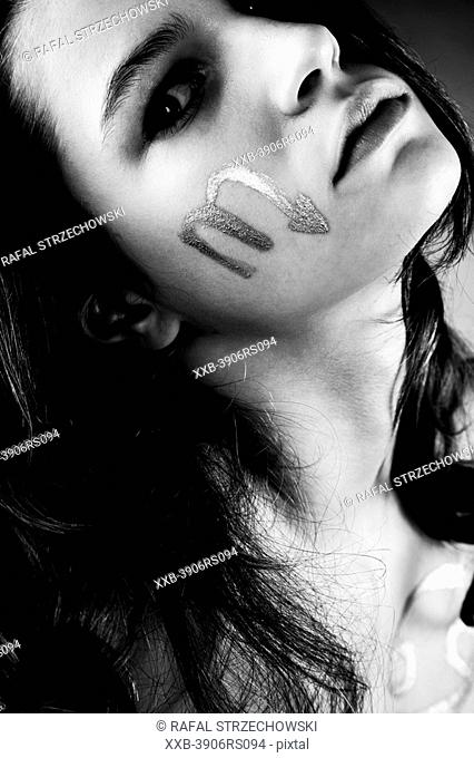 young woman with scorpio sign on cheek