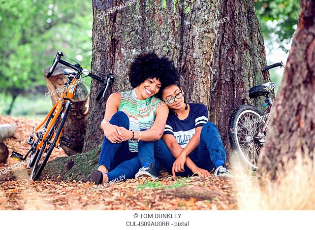 Mature woman and son sitting against park tree