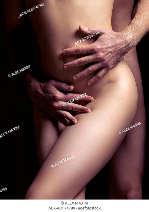 Sensual couple artistic photo. Man hands embracing naked woman body