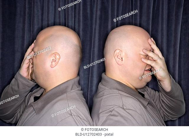 Profile of bald identical twin men standing back to back and grimacing with hands to head