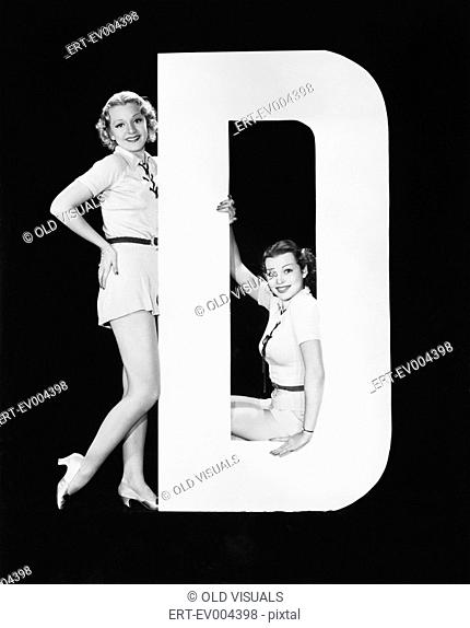 Women posing with huge letter D All persons depicted are not longer living and no estate exists Supplier warranties that there will be no model release issues