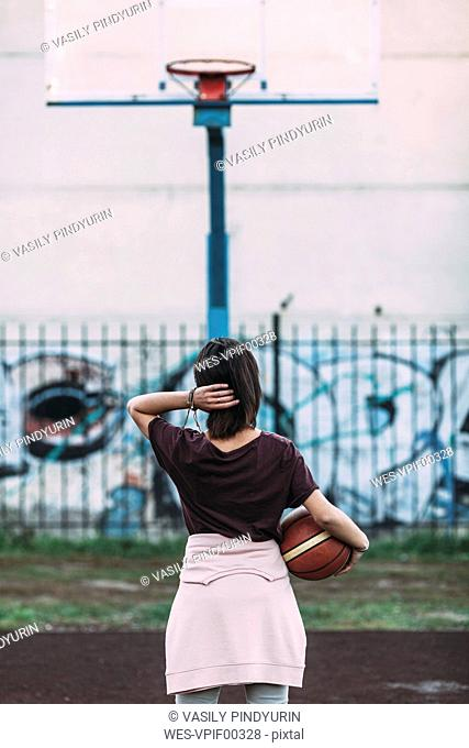 Rear view of young woman standing with basketball on outdoor court